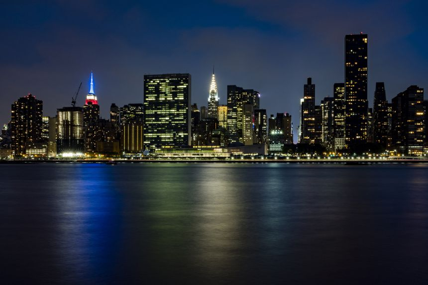 A scene looking at the New York skyline after dark with lights on in the buildings.