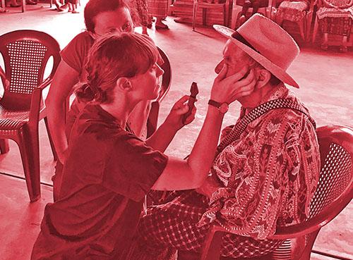 Female administers eye test on man in Guatemala