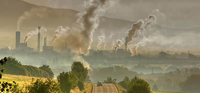 Smoke pours from smokestacks in the distance. A road runs through a hilly rural area in the foreground.