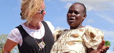 A blond UW professor and a Kenyan woman have their arms around each other.