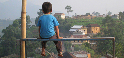 A little Nepalese boy in a blue shirt sits on a railing looking out over his village.
