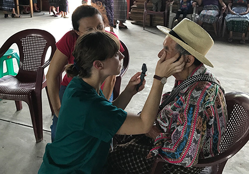 Woman examines man's eyes
