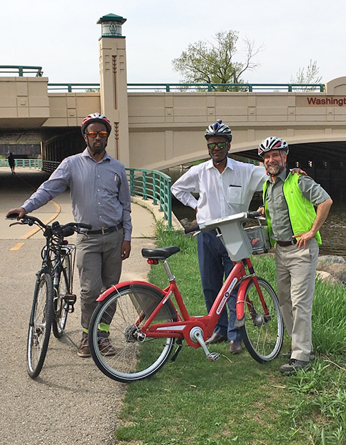 Three men, two from Ethiopia, and one from Madison stand with two bicycles on Madison's bike path.