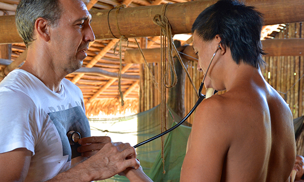 A man from the Amazon rainforest holds a stethoscope to Dr. Eric Jennings Simoes chest.